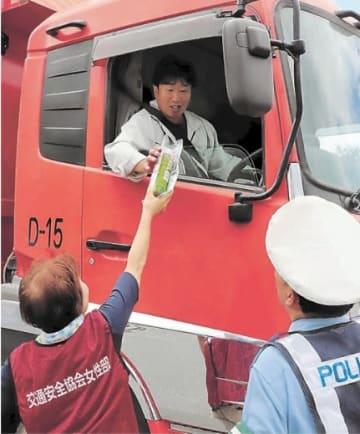 運転手に冷たい飲み物を手渡す参加者