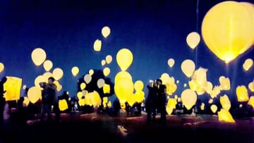 淡いオレンジの光りを浮かべて夜空を彩るスカイランタン(福知山市中・三段池公園大はらっぱ)