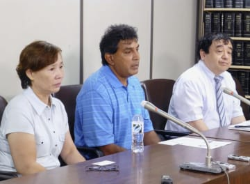 東京地裁に提訴し記者会見するモハメド・サディクさん(中央)ら=19日午後、東京・霞が関の司法記者クラブ