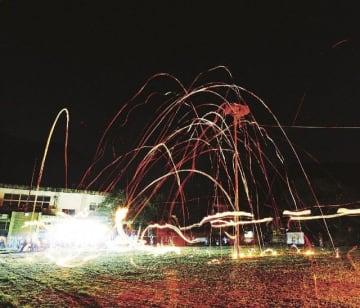高さ約8メートルの「巣」を目掛け、学生らが投げたたいまつの炎の弧=17日、和歌山県すさみ町佐本中で