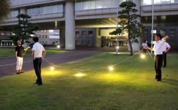 「県庁前ナイトマルシェ」で使用する電球の点灯実験を行う県職員=新潟市中央区新光町
