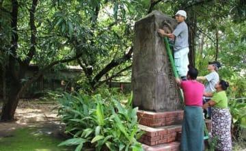 72年前に建立された鎮魂の碑をはしごに上って修復する湊さん=19日、ヤンゴン(NNA)