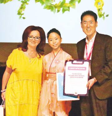ボードルさん(左)から参加証を受け取った西島校長(右)と小川さん