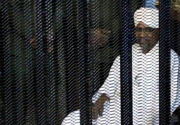 19日、ハルツームの裁判所で、おりの中に座るバシル前大統領(ロイター=共同)