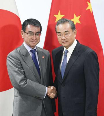 会談前に握手する中国の王毅国務委員兼外相(右)と河野外相=20日、北京郊外(共同)