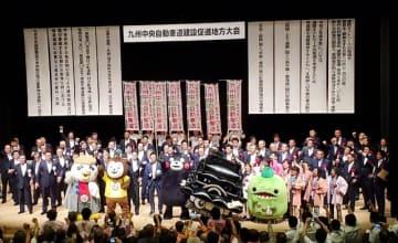 九州中央自動車道の早期完成に向けてガンバロー三唱をする参加者=20日午後、熊本県嘉島町(熊本県提供)