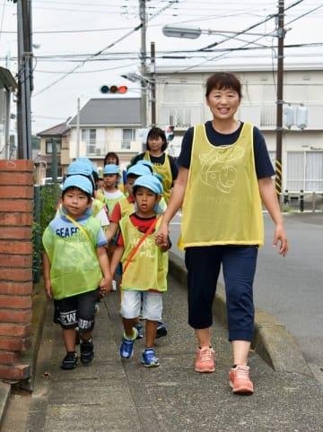ベストを着用して園外を歩く保育園児や保育士=愛川町中津