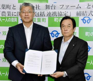 協定書に調印した伊沢町長(右)と針生社長