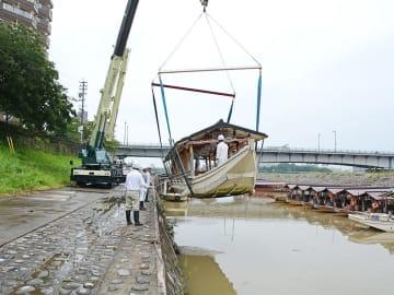 クレーンを使って係留所に戻される鵜飼観覧船=20日午前9時54分、岐阜市、長良川