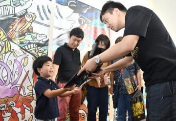 2万人目の来場者となり、石村さん(右)から記念品を受け取る直太朗ちゃん(左)