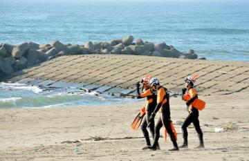 行方不明になった男子大学生が泳いでいたとみられるヘッドランド(奥)付近で、捜索が行われた=18日午後3時51分、酒田市浜中