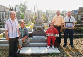 須ヶ原さんの墓参りをした旧蘭東中11期生。安部さん(右)は同期会の写真を持参した