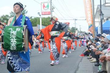 そろいの衣装を着て街頭で踊りを披露する参加者