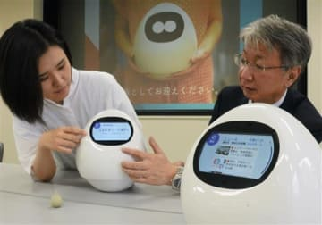 見守りロボット「タピアプレス」の使い方を説明する担当者=20日、熊本市中央区の熊日本社