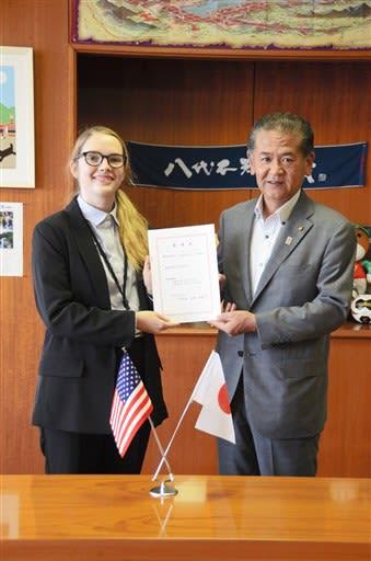 中村博生市長(右)から辞令を受け取ったジョセフィン・シャノン・デニスさん=八代市