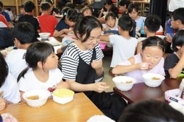 八千把小の児童らと一緒にカレーを食べる八代高生=八代市