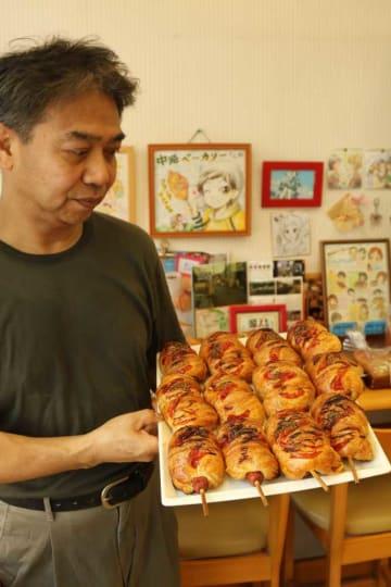 「秀一パン」とも呼ばれるフランクデニッシュを手にする中路さん。店内にはファンから贈られたという絵が多数飾られている(同市五ケ庄)