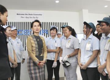 ティラワ経済特区のフォスター電機の工場で、従業員と交流するアウン・サン・スー・チー氏(左から4人目)=21日、ミャンマー・ヤンゴン近郊(共同)