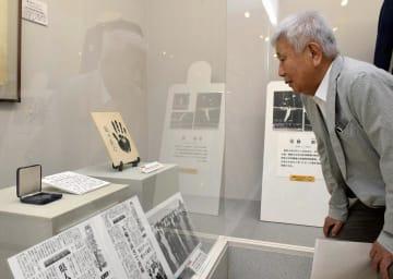 鶴田義行の展示コーナーに加わった色紙や新聞を眺める梶川さん