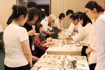 秋田県産青パパイヤの漬物を試食する来場者=21日、台北(NNA撮影)