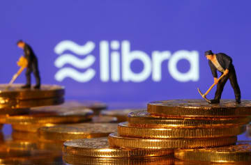 米フェイスブックが発行を計画するリブラのロゴと、仮想通貨を模した硬貨を採掘する人形=6月21日(ロイター=共同)