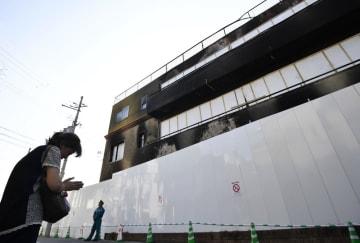 「京都アニメーション」第1スタジオの前で手を合わせる女性