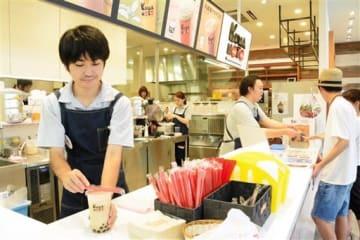 「熊本ミルクティー」健軍店でタピオカミルクティーを作る新原一季さん(左)=熊本市東区