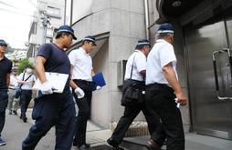 銃撃事件があった建物に入る兵庫県警の捜査員たち=22日午前、神戸市中央区熊内町9