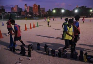 熱中症対策のため夜間練習に取り組むサッカークラブの小学生たち=13日、熊本市中央区