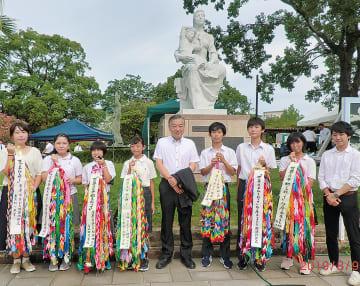 阿部市長と東京純心大学の学生サポーターと平和祈念式典に参列し、千羽鶴を献納した=多摩市提供
