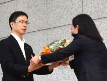 職員から花束を贈られる荻沢氏(左)