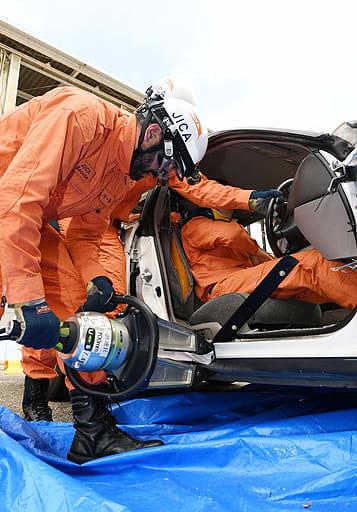 ドライバーを救出するために救助資機材で車のドアの周りを広げる研修生=22日、東大阪市