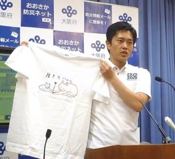 デザイナーの黒田さんがデザインしたTシャツを手に基金への寄付を呼び掛ける吉村知事=21日、府庁