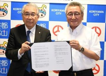 協定書を交わす品川市長(左)と出村学部長