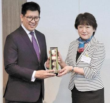 郡市長から記念品のこけしを受け取るエークニティ会長(左)