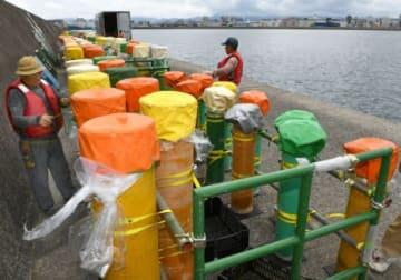 沖堤防で一尺玉花火を打ち上げる筒の準備をする花火師ら=鹿児島港本港区