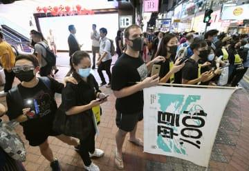 「逃亡犯条例」改正案の撤回などを求め、繁華街で「人間の鎖」をつくる市民ら=23日、香港(共同)