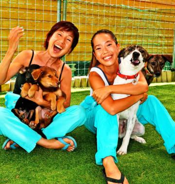 県動物愛護管理センターから引き取った保護犬たちと触れ合う(左から)平野しえさんと娘のなゆたさん=7月27日、沖縄市登川
