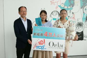 4万人目の来場者となった有冨道代さん(中央)と娘のすずさん(右)=23日、県立美術館