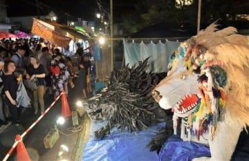 グランプリに選ばれた本町四丁目の造り物「ブラック・ライオン ホワイト・ライオン」を見物する親子連れら=23日夜、宇土市(高見伸)