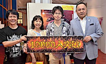 1万人目となった鈴木さん親子(中央)=23日、倉吉市鍛冶町1丁目の円形劇場くらよしフィギュアミュージアム