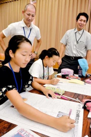 保内町商工会青年部のメンバーら(奥)に教わりながら、新聞を作る子どもたち