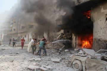 空爆を受けた建物を消火しようとする住民ら=15日、シリア北西部イドリブ県アリハ(「SY24」カメラマン、バッシャール・シェイクさん撮影・共同)