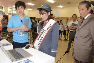 パソコンを操作し、サイバー犯罪被害の疑似体験をする「AKB48」元メンバーの小嶋真子さん(中央)。右は警視庁の斉藤実副総監=24日、東京都千代田区