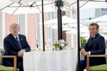 24日、フランス南西部ビアリッツで席に着くフランスのマクロン大統領(右)とトランプ米大統領(AP=共同)