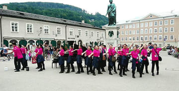 オーストリア・ザルツブルクのモーツァルト像の前で軽快な歌と踊りを披露するメンバー