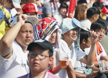 強烈な日差しの中でも夏の甲子園では熱心な観戦客が(C)共同通信社
