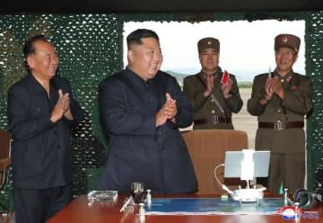「新型ロケット砲」の試射を指導する北朝鮮の金正恩朝鮮労働党委員長(中央)。机の上にはiPadとみられるタブレットが写っている=24日(朝鮮中央通信=共同)