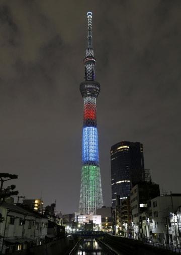 東京パラリンピック開幕まで1年となったのを記念して、シンボルカラーにライトアップされた東京スカイツリー=25日夜、東京都墨田区