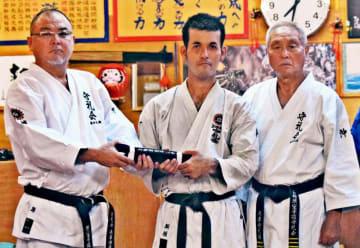 初段合格を果たした新垣巧巳さん(中央)に黒帯を手渡す島袋淳館長(左)、島袋常雄首席師範=17日、うるま市勝連